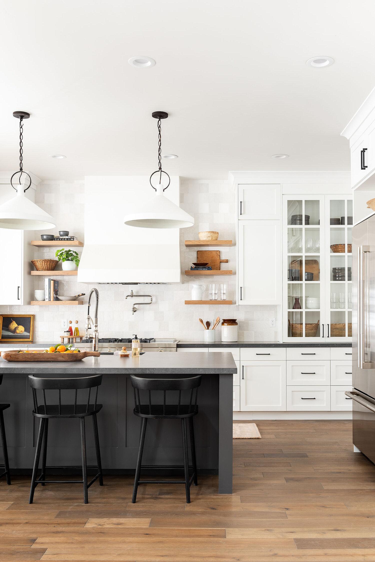 Bílá kuchyň s černým barovým pultem