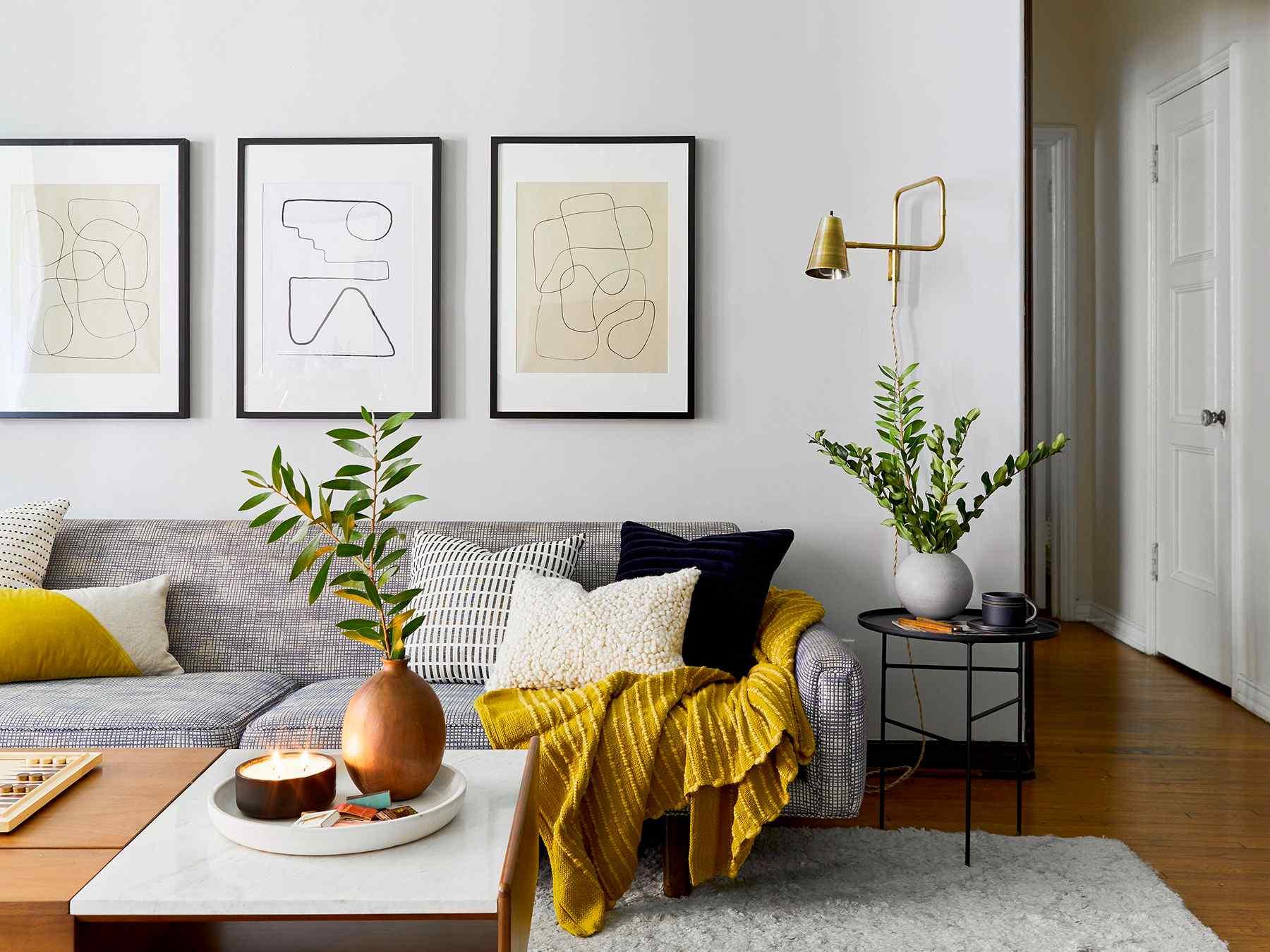 Gauč s polštáři a grafikami na stěne