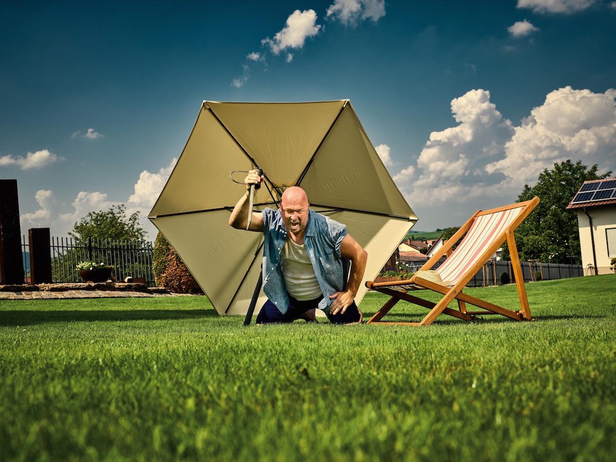Muž zapichující slunečník do trávy