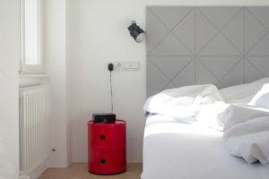 Sivá geometrická postel a rudý okrouhlý stolek