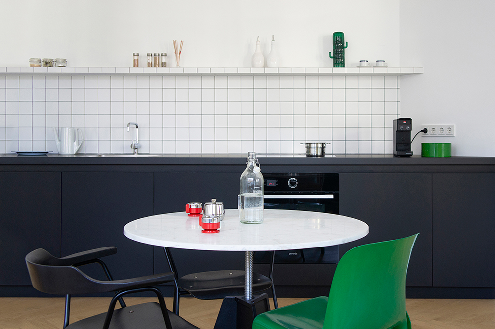 Černá kuchyň s bílou stěnou zelené detaily