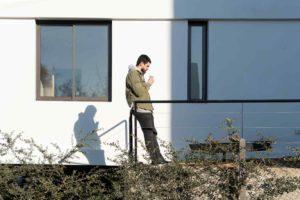 Muž na terase bílého domu kouří