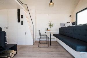 Interiér malé chatky s gaučem spícím prostorem