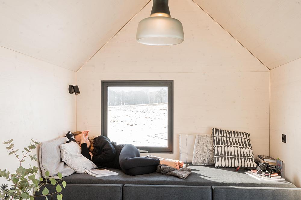 Mobilní domek pohodlným gaučem a velkým oknem