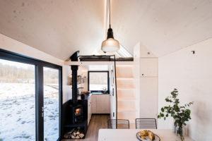 Interiér malé chatky s krbem a spícím prostorem