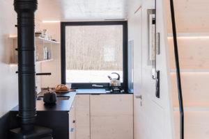 Kuchyň v chatce s krbem a spícím prostorem