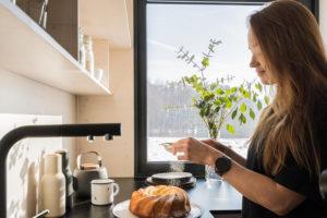 Žena posýpá bábovku cukrem v kuchyni