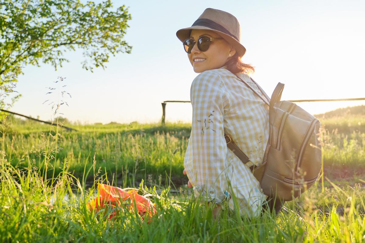 Žena na louce v brýlých a klobouku