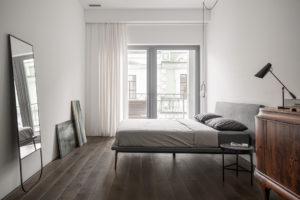 Ložnice s velkým oknem a starožitnou komodou
