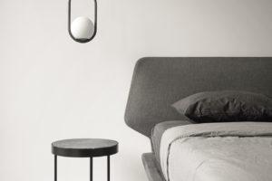 Dizajnové svítidlo na okrouhlým stolkem v ložnici