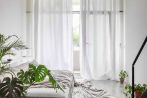 Velká bílá pohodlná postel v loftu
