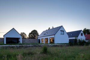 Bílé domky se sedlovou střechou spojené zdí