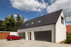 Bílá garáž s antracitovou střechou a rudým autem