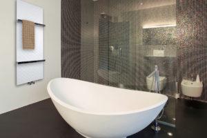 Bílý tenký radiátor v koupelně s volně stojící vanou