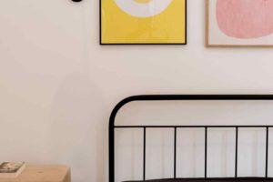Ložnice s černou postelí a grafikami