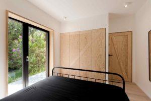 Ložnice s černou postelí a překližkovou stěnou