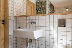 Bílošedá mozaiková koupelna s toaletou