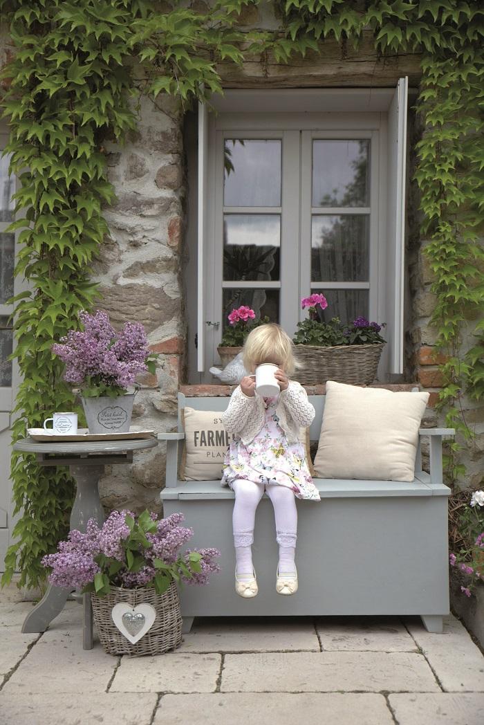Hannah si vychutnává šálek voňavého čaje na staré lavičce