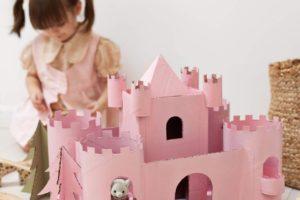 Holčička pri rúžovém hradě z kartonu