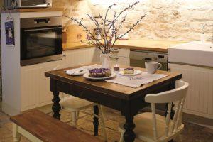 Dřevěný vyřezávaný jídelní stůl, lavice i židle v starodávné kuchyni