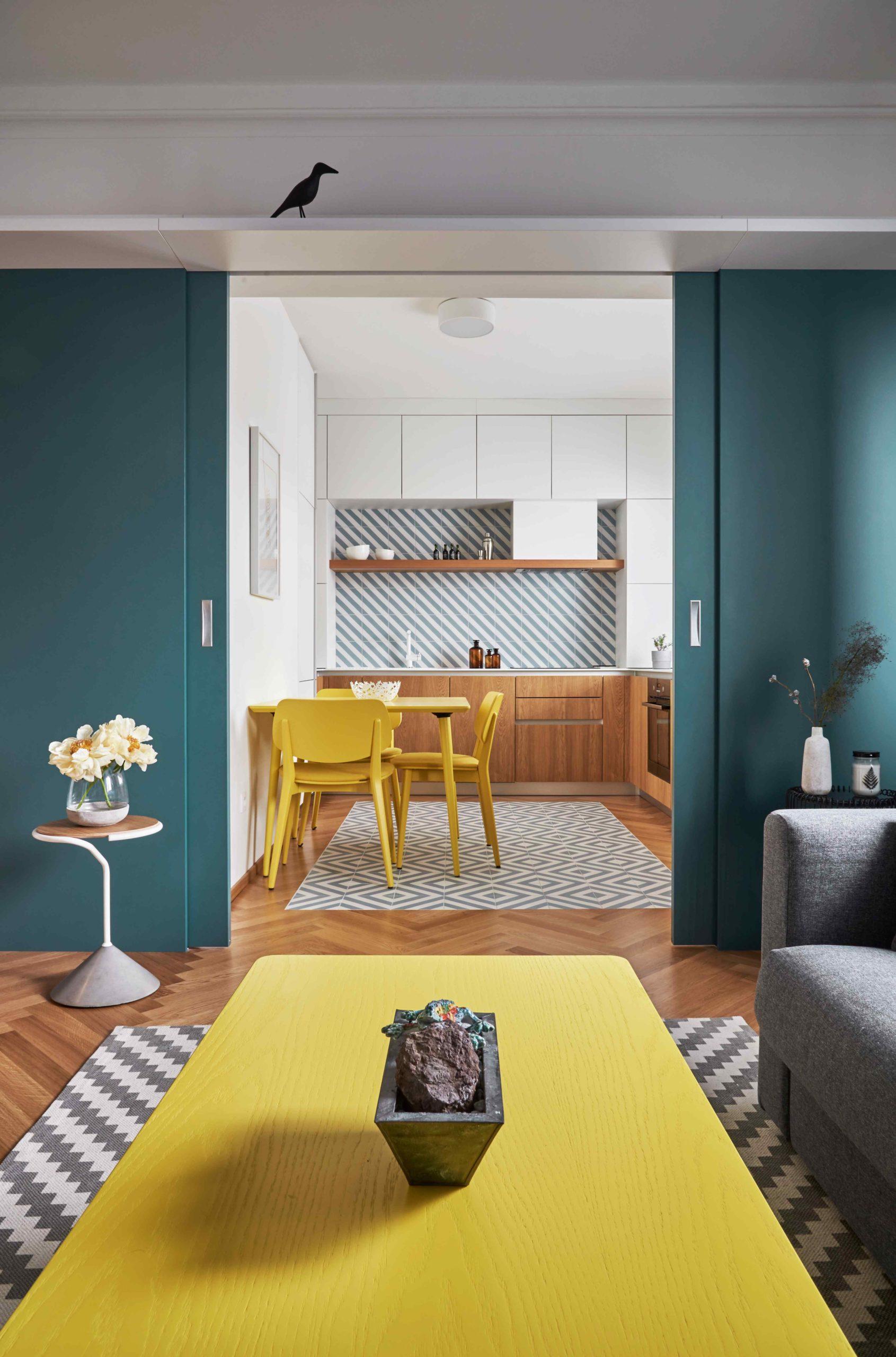 Obývák se zelenými posuvnými dveřmi do biílé kuchyně