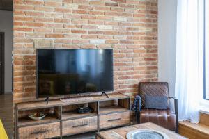 Televize s drevěným stolkem před tehlovou stěnou