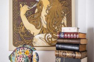 Alfonz Mucha obraz nad komodou s knihami