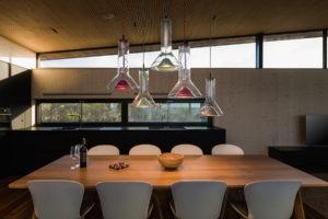 Jídelna s dizajnovým lustrem v kuchyni víkendového domu