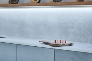 Sivá kuchyň s ostrůvkem a přírodními dekoracemi
