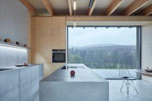 Sivá kuchyň s ostrůvkem a velkým oknem