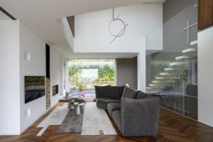 Moderní obývací pokoj s prosklenou stěnou a krbem