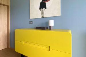 Žlutá komoda s obrazem a modrou stěnou