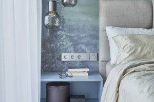 Modrá ložnice s tapetou a dizajnovými svítidlami