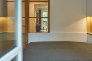 Velká jednoduchá postel v bílé ložnici