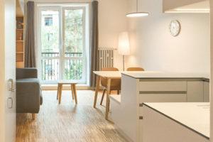 Kuchyň s dřevěnou podlahou a bílou linkou