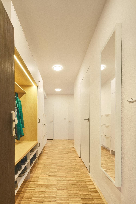 Chodba v bílé s dřevěnou podlahou