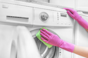 Žena čistí pračku v rukavicích