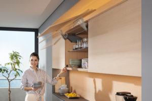 Žena v kuchyni otevírá vyklápací skříňky