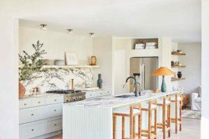 Bílá kuchyň s ostrúvkem a barovými židlemi