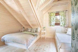 Zelená ložnice v srubu s dekorem kapradí