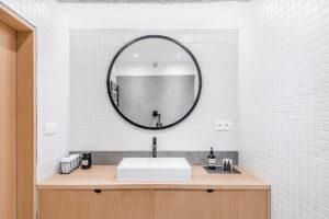Bílá koupelna s betonóvým prvkem a dřevěným nábytkem