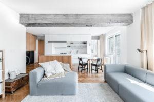 Svetlý obývák spojený s kuchyní s betonovým pilířem