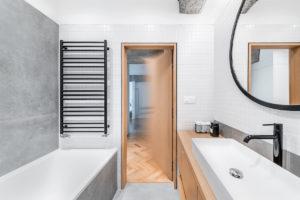 Bílá koupelna s dřevěným nábytkem a šedou stěnou