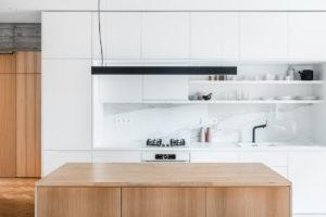 Bílá kuchyňská linka s dřevěným ostrúvkem