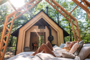 Chatka s otevřenou střechou a ležící žena na posteli