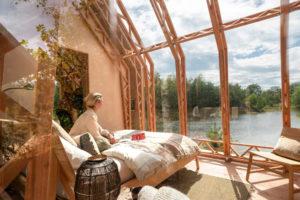 Chatka s otevřenou střechou a sedící žena na posteli