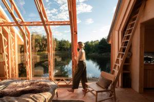 Chatka s otevřenou střechou a stojící žena