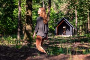 Žena v lese před chatou