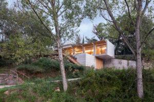 Obdélnikový presklený dům ukrytý ve svahu