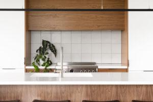 Bílý box v kuchyni s drevěným barovým pultem